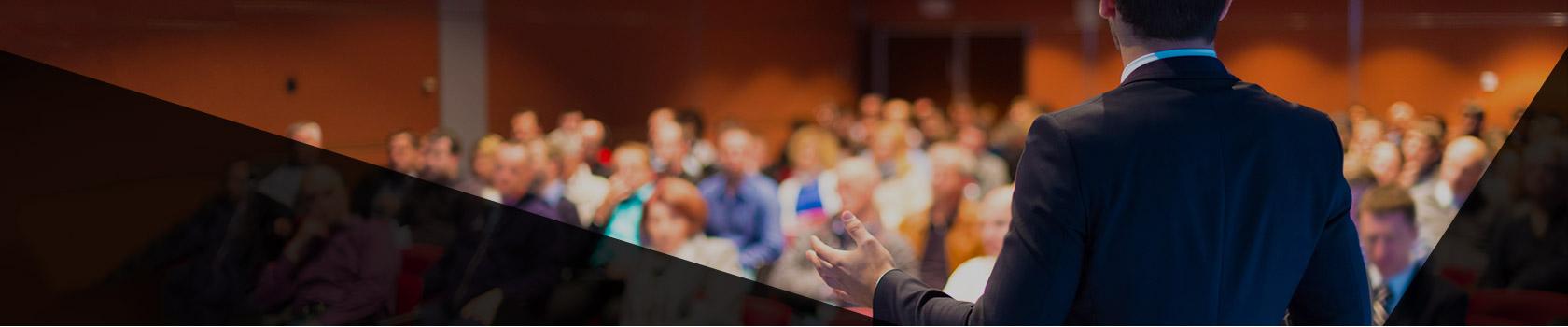 Schulungen und Seminare Header, Foto von Sprecher mit Publikum